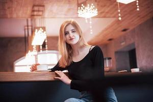 Happy smiling young woman using phone in a cafe. Beautiful girl in trendy spring colors photo