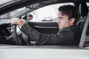 listo para la prueba de manejo. retrato, de, un, guapo, hombre de negocios, conduciendo coche foto
