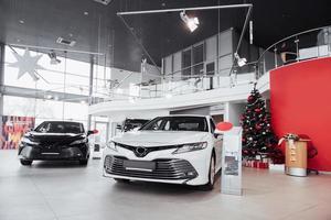 New shining beautiful cars stand near desk reception in car shop photo
