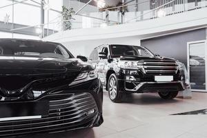Nuevos y hermosos autos brillantes están parados cerca del mostrador de recepción en la tienda de autos foto