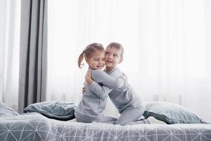 niños felices jugando en el dormitorio blanco. niño y niña, hermano y hermana juegan en la cama en pijama. interior de guardería para niños. ropa de dormir y ropa de cama para bebés y niños pequeños. familia en casa foto