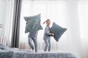 niños en pijamas suaves y cálidos jugando en la cama foto
