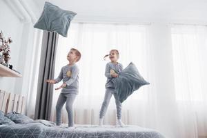 niños jugando en la cama de los padres. los niños se despiertan en la soleada habitación blanca. niño y niña juegan con pijamas a juego. ropa de dormir y ropa de cama para niño y bebé. Interior de guardería para niños pequeños. mañana familiar foto