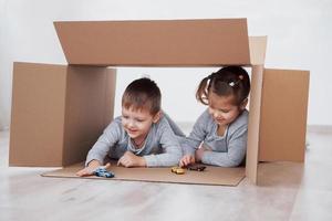 Hermano y hermana infantil jugando en cajas de cartón en la guardería foto