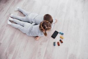 vista superior. niños que utilizan dispositivos digitales en casa. hermano y hermana en pijama ven dibujos animados y juegan juegos en su tableta tecnológica foto