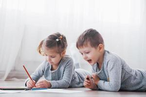 Children lie on the floor in pajamas and draw with pencils. Cute child painting by pencils photo