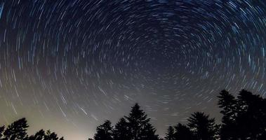 Star trails over the night sky - comet mode, Time lapse of star trail, pine trees in the foreground, Avala, Belgrade, Serbia. The night sky is astronomically accurate. video