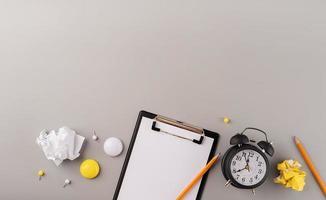 Papel en blanco en el portapapeles, reloj despertador blanco y vista superior de papelería sobre fondo gris foto