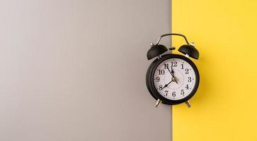 Despertador retro negro aislado sobre fondo gris y amarillo doble con espacio de copia foto