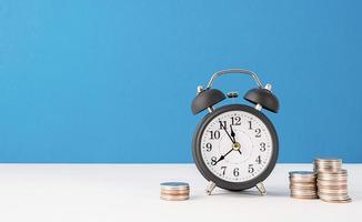 Despertador retro negro con monedas sobre fondo azul. foto