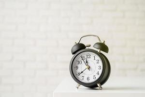Despertador retro negro sobre fondo de pared de ladrillo blanco con espacio de copia foto