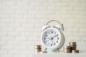 Despertador retro blanco con monedas sobre fondo de pared de ladrillo blanco foto