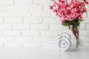 Despertador retro blanco sobre pared de ladrillo blanco con libros y flores con espacio de copia foto