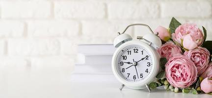 Despertador retro blanco sobre pared de ladrillo blanco con libros y peonías con espacio de copia foto