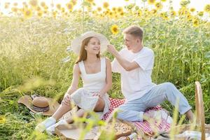 Young couple having picnic on sunflower field photo
