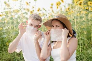 Young couple having picnic on sunflower field at sunset, making funny faces photo
