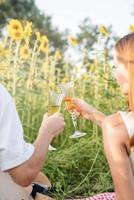 Young couple having picnic on sunflower field at sunset photo