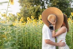 Joven pareja feliz besándose en una manta de picnic, cubriendo sus rostros con un sombrero de verano foto