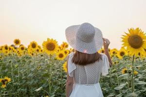 Hermosa mujer joven con sombrero de pie entre girasoles al atardecer foto
