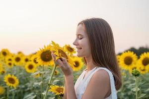 Girl in white dress smelling a sunflower blossom. photo
