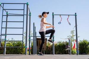 Sportive woman working out on the sports ground in sunny summer day photo
