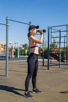 Young sportive woman in sport gloves drinking water on sport ground photo