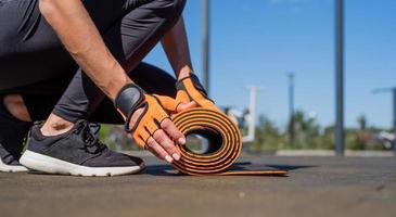 Primer plano de una mujer con las manos en los guantes deportivos Rolling fitness mat preparándose para entrenar foto