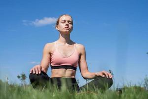 Sportive woman meditating sitting on grass under blue sky photo
