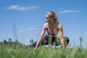 Sportive woman working out in the park in sunny summer day photo