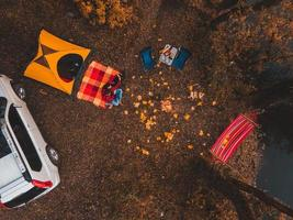 Overhead top view of autumn camping site with tent car hammock bonfire photo