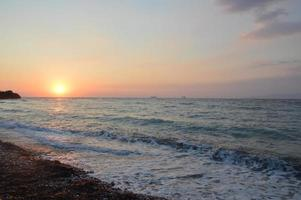 Sunset on the shore of the Agean Sea in Rhodes in Greece photo