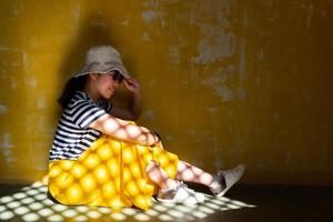 Young beautiful asian woman wearing hat, sunglasses, and yellow skirt that has sunlight on surface. She sit on the floor with grunge peeled scratch yellow background photo