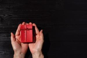 Top view of  hand of woman give present box in christmas photo