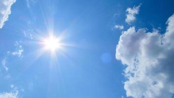 Sun, sky and clouds. Sun on the background of a blue sky with white clouds photo