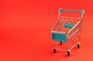 Carro de compras vacío sobre fondo rojo brillante foto