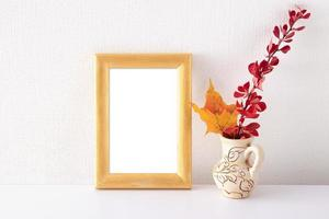 Empty golden frame mockup in white interior near vase with autumn leaves photo