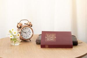 Bible and notebook on the table with an alarm clock by the window. Time for learning Bible concept photo