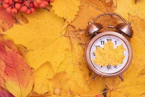 otoño hojas de otoño y despertador. concepto de tiempo de otoño creativo foto