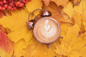 Coffee art in an alarm clock on a background of fallen leaves. Autumn time and morning coffee concept photo