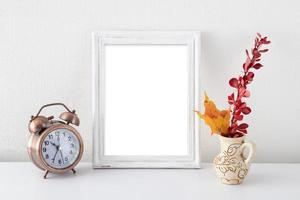 Mock up empty white frame in white interior near vase with autumn leaves and alarm clock photo