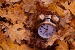 otoño hojas de otoño y despertador. concepto de tiempo de otoño foto