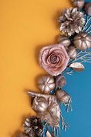 Flat lay calabazas doradas y bellotas sobre un fondo naranja-turquesa foto