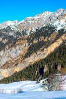 Panorama de la montaña con dos escaladores en la distancia en la nieve. foto