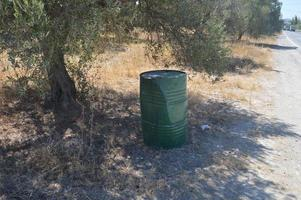 A green metal barrel stands in the shade of a tree photo