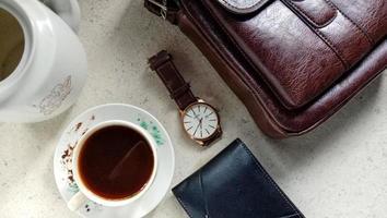 Fotos planas de productos para hombres en forma de relojes, carteras y bolsos de cuero, así como una taza de café.