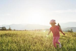Cute happy little baby girl play outdoors in the lawn and admiring mountains view. Copy space for your text photo