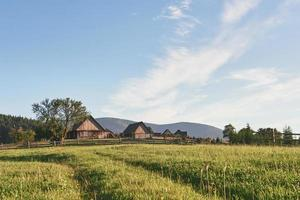 Village houses on hills with green meadows in summer day. House of shepherds in mountains in carpathian photo