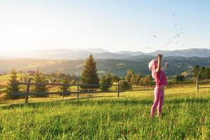 Cute happy little baby girl play outdoors in the early morning in the lawn and admiring mountains view. Copy space for your text photo