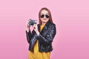 Look de moda, modelo de mujer joven muy guay con cámara de película retro con una chaqueta negra, contra un fondo rosa con espacio de copia foto