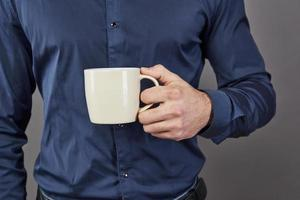 Handsome bearded man with stylish hair beard and mustache on serious face in shirt holding white cup or mug drinking tea or coffee in studio on grey background photo